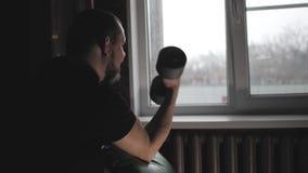 Hombre joven que se resuelve en el gimnasio casero que hace ejercicios con pesas de gimnasia en los bíceps Hombre atlético del po metrajes