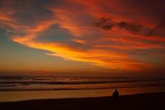 Hombre joven que se sienta al aire libre mirando la puesta del sol Concepto de pensamiento y de relajaci?n, Australia foto de archivo