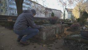 Hombre joven que se sienta cerca de sepulcro en el cementerio antiguo que ruega, estando de luto para los parientes almacen de video