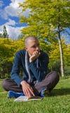 Hombre joven que se sienta con el libro en parque foto de archivo libre de regalías
