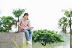 Hombre joven que se sienta con el ordenador portátil fuera del edificio de la universidad Fotos de archivo libres de regalías