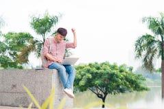 Hombre joven que se sienta con el ordenador portátil fuera del edificio de la universidad Fotografía de archivo