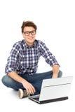 Hombre joven que se sienta con la computadora portátil Foto de archivo libre de regalías