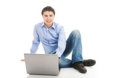Hombre joven que se sienta con la computadora portátil Fotos de archivo libres de regalías
