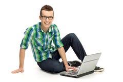 Hombre joven que se sienta con la computadora portátil Imágenes de archivo libres de regalías