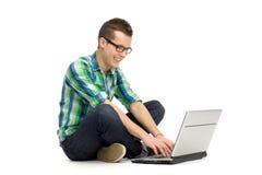 Hombre joven que se sienta con la computadora portátil Imagen de archivo
