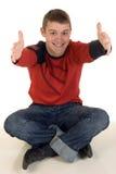 Hombre joven que se sienta con los brazos extendidos Foto de archivo libre de regalías