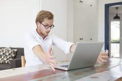 Hombre joven que se sienta con su ordenador portátil y que parece subrayado y excit Imagenes de archivo
