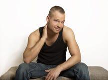 Hombre joven que se sienta con una mano en su cabeza Fotos de archivo libres de regalías