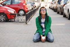Hombre joven que se sienta contra un estacionamiento del coche Fotos de archivo