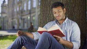 Hombre joven que se sienta debajo del libro de lectura del árbol y que piensa, literatura, ficción almacen de metraje de vídeo