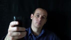 Hombre joven que se sienta delante de la cámara y de los interruptores los canales, TV de observación almacen de metraje de vídeo
