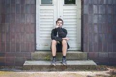 Hombre joven que se sienta delante de una puerta en las escaleras Foto de archivo libre de regalías