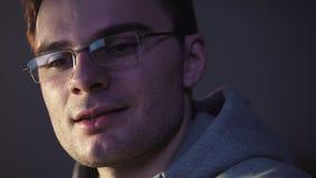 Hombre joven que se sienta delante del comienzo del ordenador que sonríe consiguiendo un achivement almacen de video