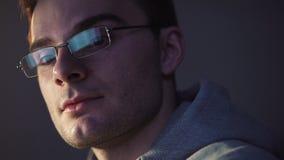 Hombre joven que se sienta delante del comienzo del ordenador que sonríe consiguiendo una brecha almacen de video