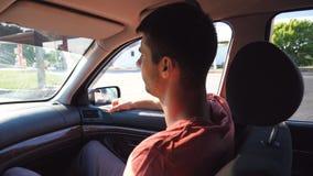 Hombre joven que se sienta dentro del coche móvil en asiento de pasajero y que mira la ventana Perfil del individuo hermoso que v almacen de metraje de vídeo