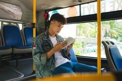 Hombre joven que se sienta en autobús de la ciudad y que lee un libro fotografía de archivo