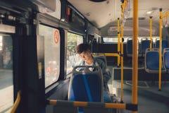 Hombre joven que se sienta en autobús de la ciudad y que lee un libro Imagenes de archivo