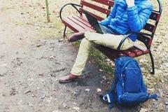 Hombre joven que se sienta en banco con el ordenador portátil en parque Imagen de archivo