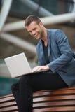Hombre joven que se sienta en banco con su computadora portátil Imagenes de archivo