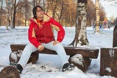 Hombre joven que se sienta en banco en parque del invierno Foto de archivo libre de regalías
