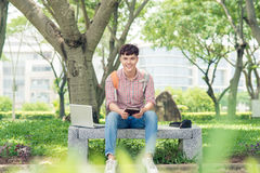 Hombre joven que se sienta en banco en parque, libro de lectura, la sonrisa y el lo Imagen de archivo libre de regalías