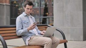 Hombre joven que se sienta en banco mientras que trabaja en línea almacen de video
