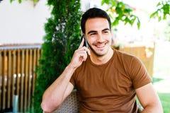 Hombre joven que se sienta en café y que habla en el teléfono Fotografía de archivo libre de regalías