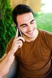 Hombre joven que se sienta en café y que habla en el teléfono Imagen de archivo libre de regalías