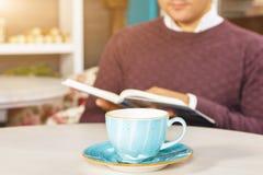 Hombre joven que se sienta en café y que lee un libro Imágenes de archivo libres de regalías
