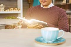 Hombre joven que se sienta en café y que lee un libro Fotografía de archivo