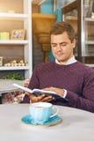 Hombre joven que se sienta en café y que lee un libro Foto de archivo libre de regalías