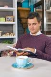 Hombre joven que se sienta en café y que lee un libro Fotos de archivo