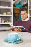 Hombre joven que se sienta en café y que lee un libro Imagenes de archivo