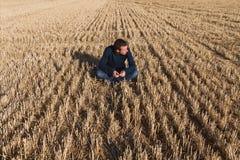 Hombre joven que se sienta en campo foto de archivo libre de regalías