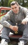 Hombre joven que se sienta en cerveza de consumición del patio Imagenes de archivo
