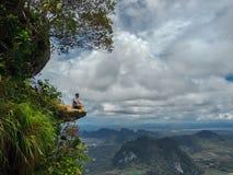 Hombre joven que se sienta en el acantilado con Mountain View magnífico imagenes de archivo