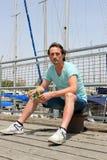 Hombre joven que se sienta en el bolardo en el embarcadero con la barrera en puerto deportivo El turista tiene resto en el día so fotos de archivo libres de regalías