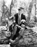 Hombre joven que se sienta en el bosque con su perro que parece desesperado (todas las personas representadas no son vivas más la Imagenes de archivo