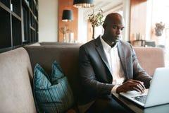 Hombre joven que se sienta en el café que trabaja en el ordenador portátil imagen de archivo