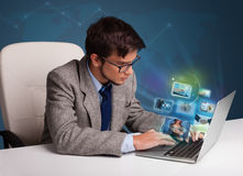 Hombre joven que se sienta en el escritorio y que mira su galería de fotos en lapt fotografía de archivo libre de regalías