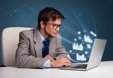 Hombre joven que se sienta en el escritorio y que pulsa en la computadora portátil con los diagramas y Imagen de archivo