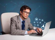 Hombre joven que se sienta en el escritorio y que pulsa en la computadora portátil con netwo social Fotos de archivo libres de regalías
