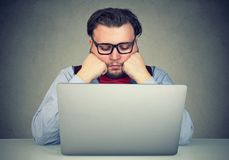 Hombre joven que se sienta en el lugar de trabajo y que procrastina siendo perezoso y distraído imagenes de archivo
