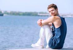 Hombre joven que se sienta en el muelle del río Fotos de archivo