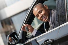 Hombre joven que se sienta en el nuevo coche que mira hacia fuera de ventana con la cámara de mirada dominante juguetona imagenes de archivo