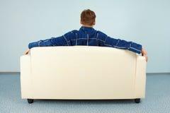 Hombre joven que se sienta en el país en el sofá imagenes de archivo