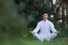 Hombre joven que se sienta en el parque que hace la meditación Imagen de archivo