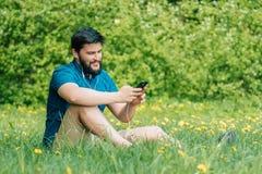 Hombre joven que se sienta en el parque y el mensaje que manda un SMS Foto de archivo