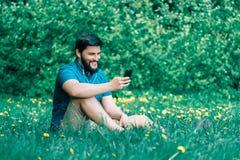 Hombre joven que se sienta en el parque y el mensaje que manda un SMS Imágenes de archivo libres de regalías